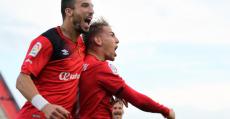 Brandon y Díaz celebrando el hattrick del santanyiner ante el Huesca. Foto: Fútbol Balear.