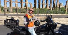 Monti Galmés posando con su motocicleta frente al puente romano de Mérida. Foto: Facebook.