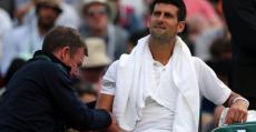Djokovic atendido del codo por el médico en Wimbledon.
